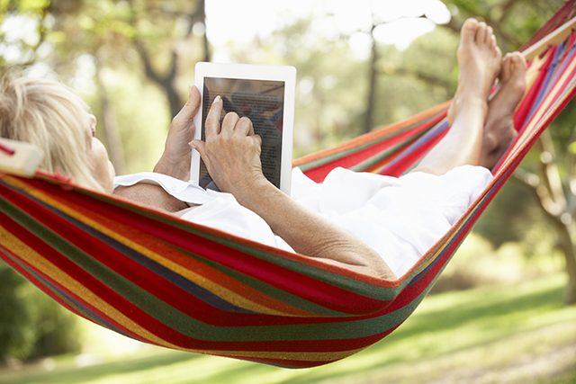 電子書籍をハンモックで読む女性